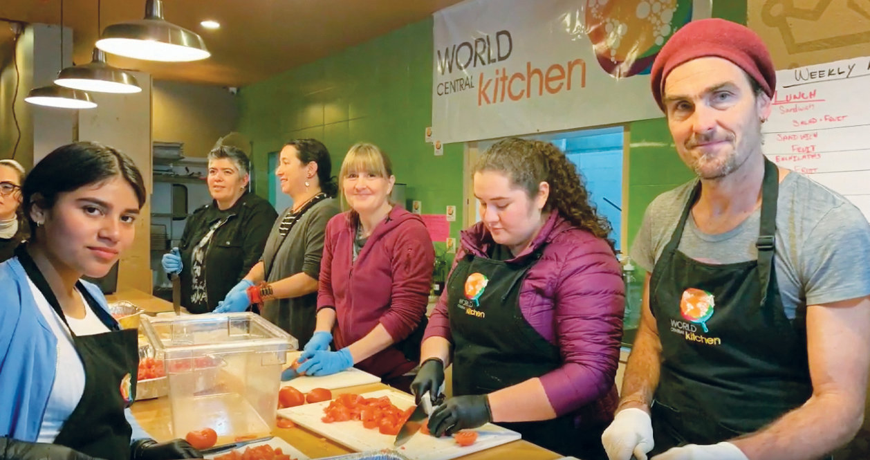 Nikki Russell, middle, works with other volunteers in Tijuana at the World Central Kitchen, which provides meals for people seeking asylum at the U.S. border.