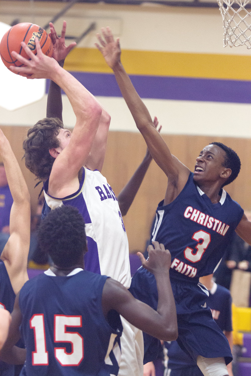 Rangers senior center Robert Comstock III goes up for a shot between Christian Faith defenders Jaylen Kimani (15) and Deshawn Kimani (3) on Jan. 30 at Quilcene High School.