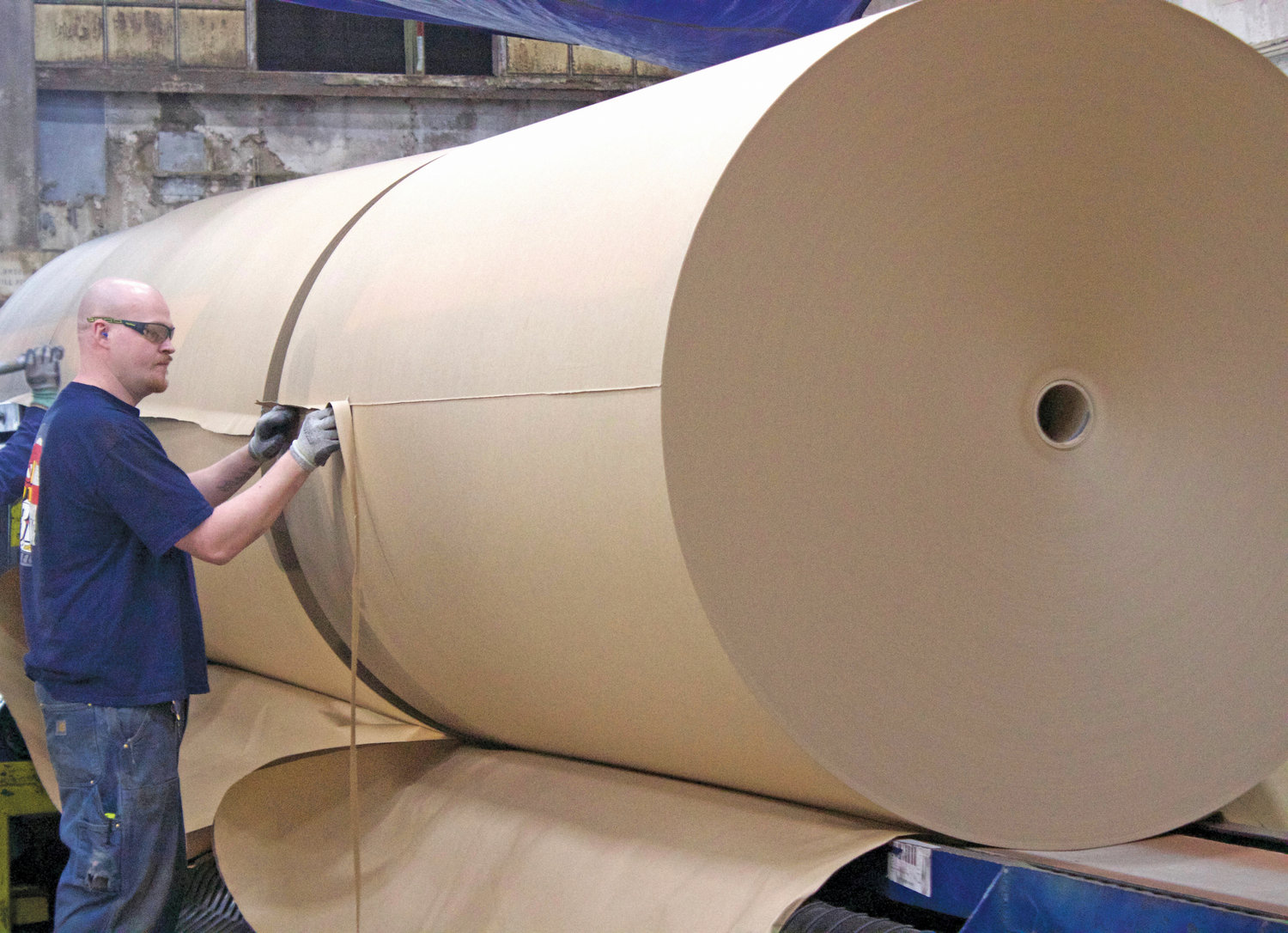 Scott Brown cuts the excess ends off a giant roll of brown paper made at the Port Townsend Paper Company.