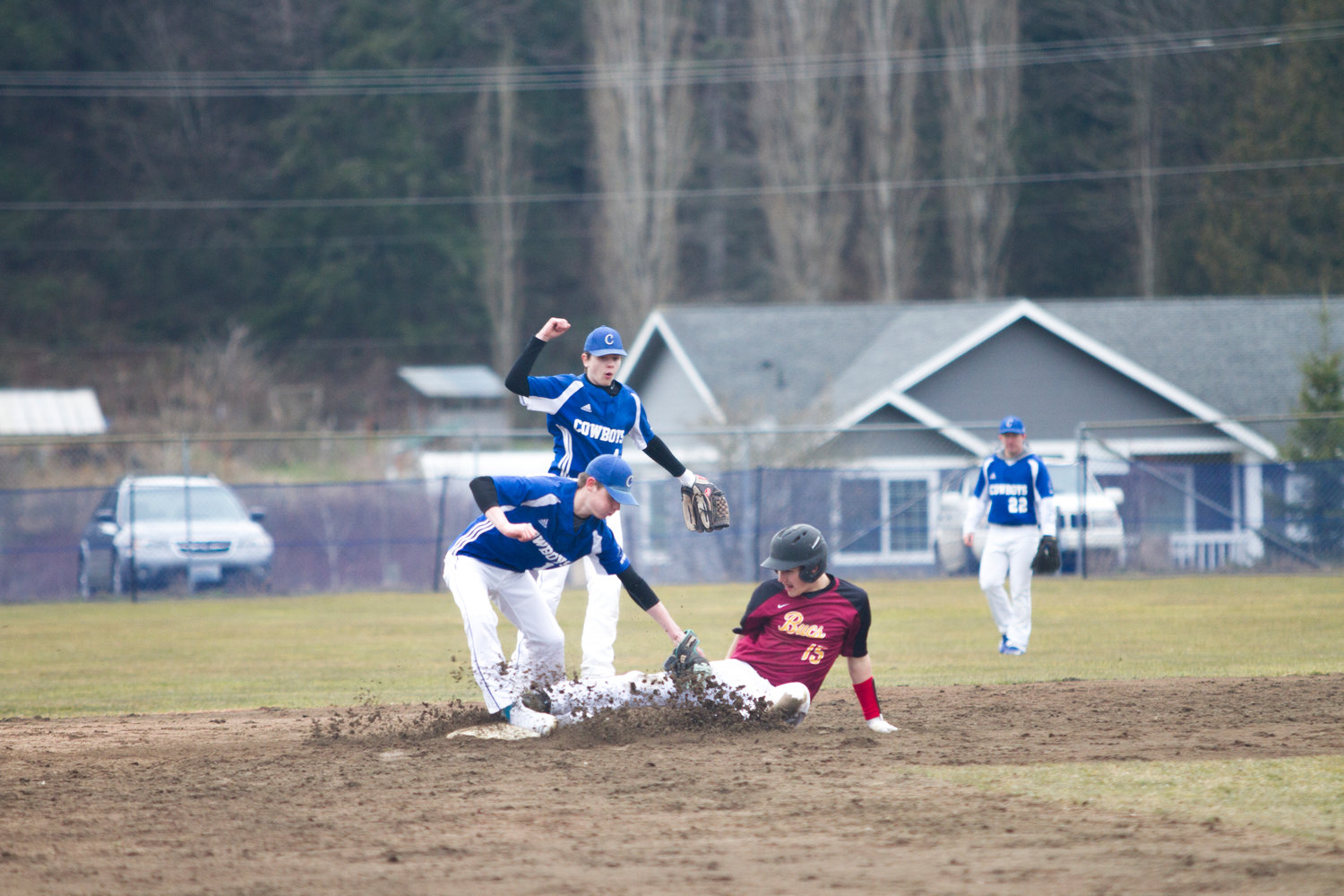 Chimacum senior Issac Purser tags Kingston's Tim Foss out as Foss slides into second base during the March 11 game at Chimacum. The Cowboys wont their season opener against Kingston 9-3.