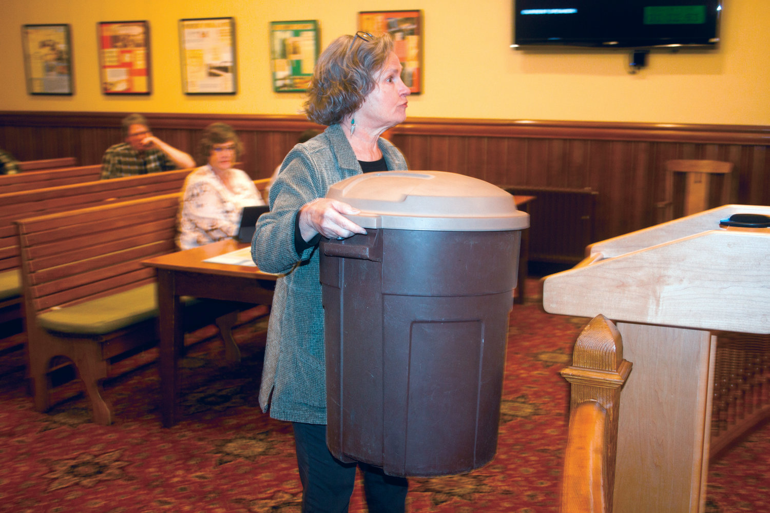 Renee Busch brought her 20-gallon bin to city council chambers to illustrate the city's failure to reward waste reduction.