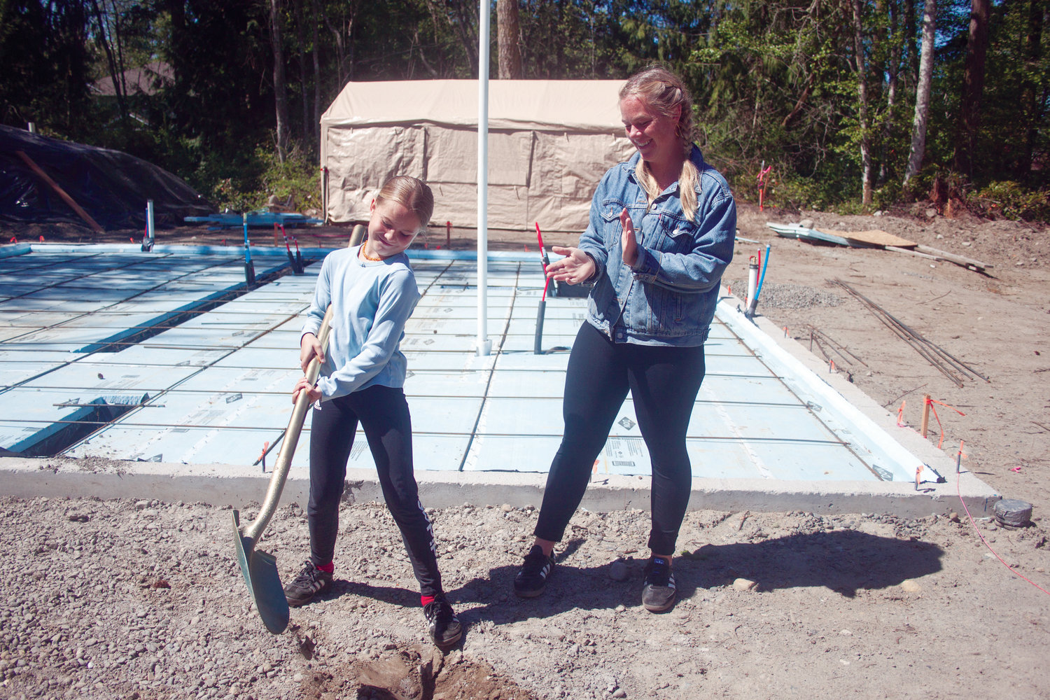 Olivia Jonland, 9, is cheered on by her mother, Ingrid, as she turns a ceremonial shovel of dirt at the foundation of their new home April 27.