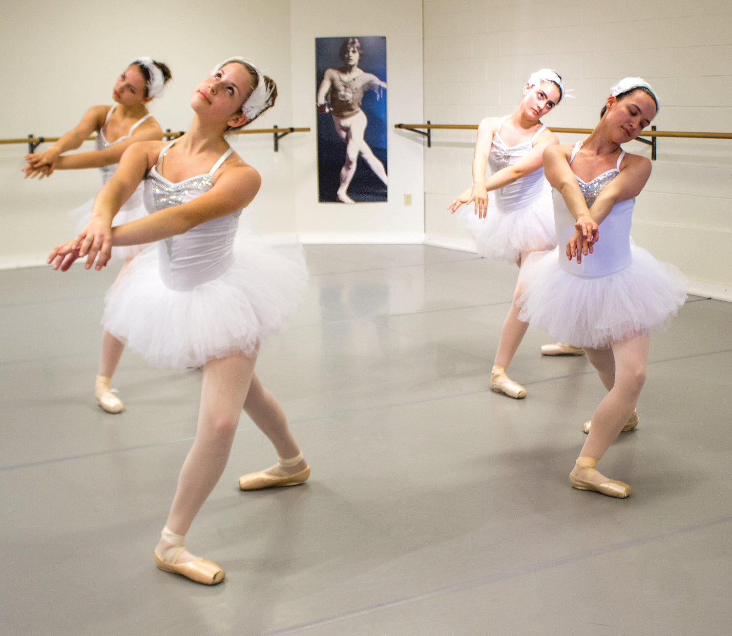 "our of Ling Hui's young adult dancers, dressed in white with feathered head-pieces, maneuvering ""en pointe"" with disciplined maturity, skill and grace."