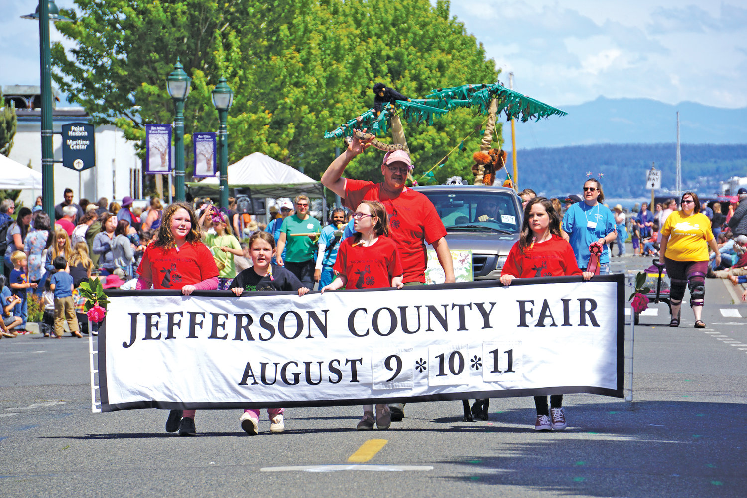 Jefferson County 4H members carry the Jefferson County Fair banner down the parade route.