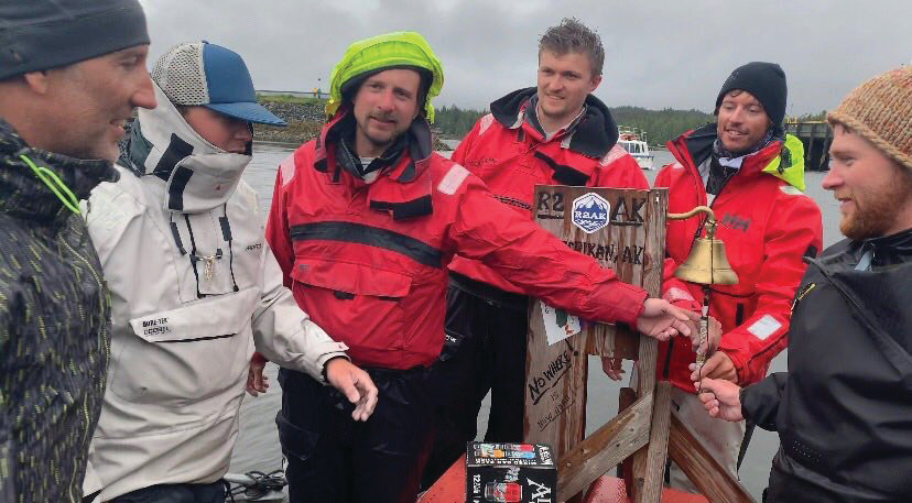 Crew of Team Angry Beaver ring the ceremonial bell at the finish line of the 2019 R2AK. From left are Mats Elf, Alan Johnson, Simon Miles, Brent Campbell, Skipper Matt Pistay and Gavin Bracket.