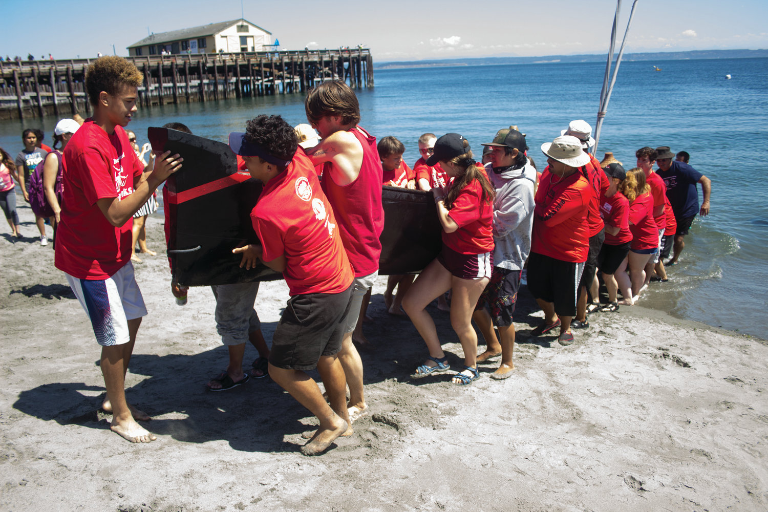 Port Townsend High School student athletes help pull canoes ashore during the arrival of last year's tribal journey to Fort Worden.