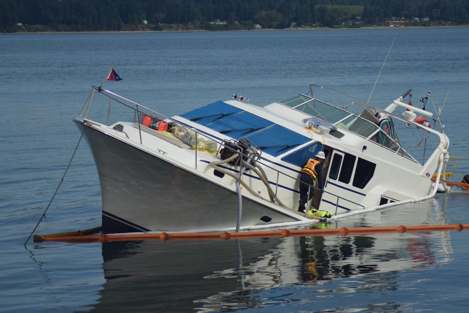 With 300 gallons of diesel in its fuel tanks, the sunken Silver Linings, a 65-foot luxury yacht, was surrounded with precautionary spill buoy to prevent any leaks from escaping beyond the recovery scene.