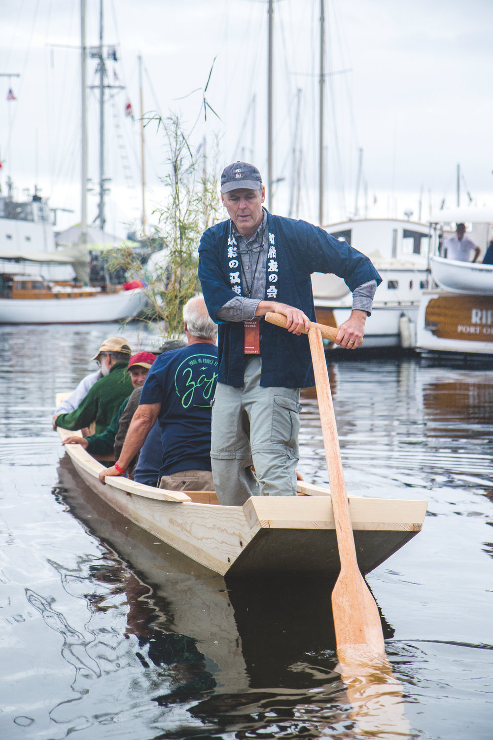 Douglas Brooks uses the sculling oar to launch the Shinano river boat with the boat builders.
