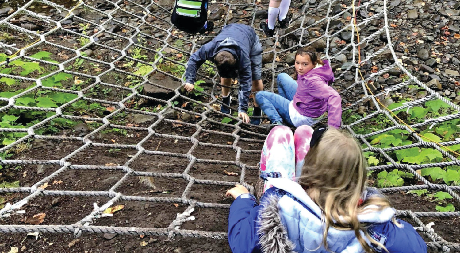 A previous class of Chimacum sixth-graders challenge themselves on a climbing net at Camp Cispus. Visiting the camp has been an annual tradition since about 1986.