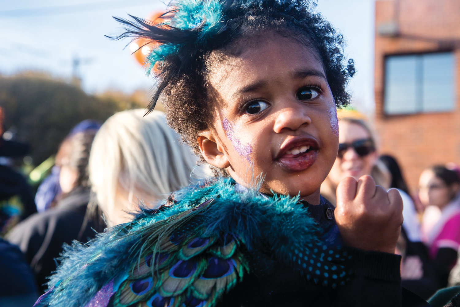 Zuri Bohannon shows off her glittering peacock feathers as she awaits Port Townsend's Halloween community photo and parade. In the arms of Kymber McLay, she is ready to visit Water Street's storefronts for some trick-or-treating.