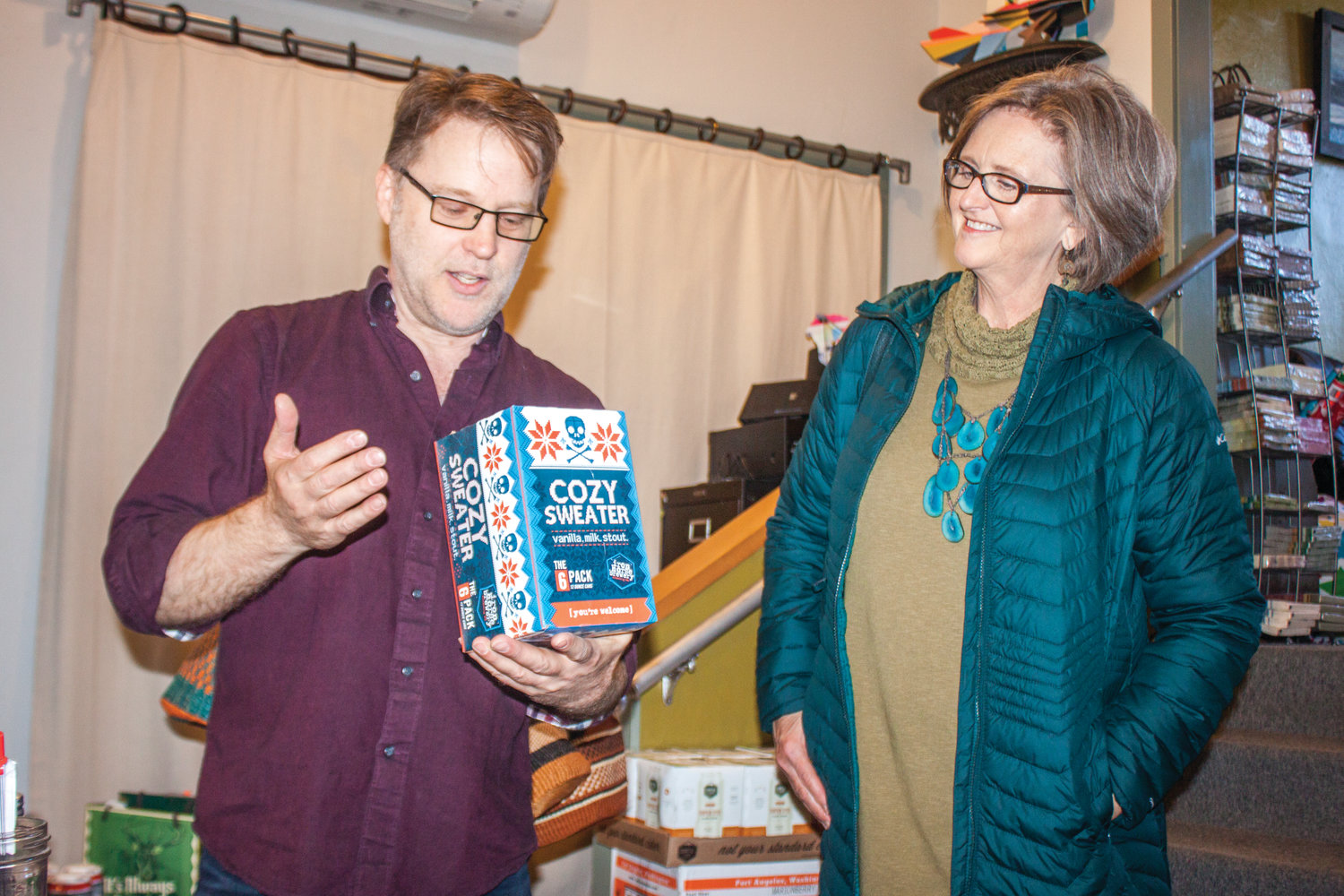 "Pat Louderback, the new owner of Getables, shows Port Townsend Mayor Deborah Stinson some of his holiday-themed merchandise, since he's ""a Christmasy guy."""