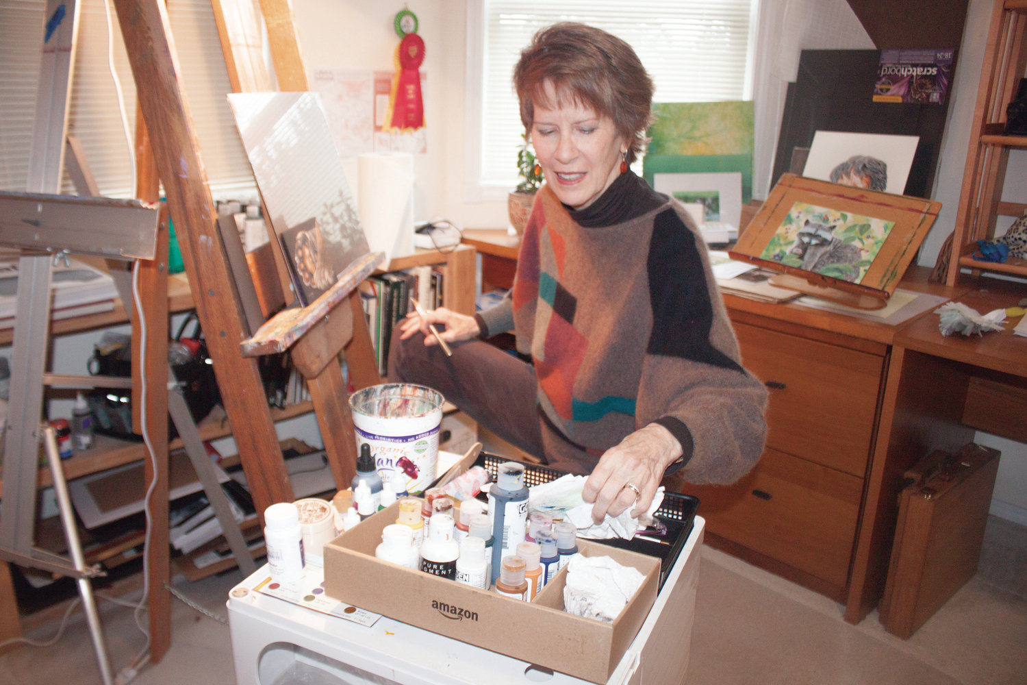 """Laurie Riley does detail work on an illustration of a paw, in the art studio upstairs from the """"Art of the Wild"""" gallery on the ground floor of her home."""