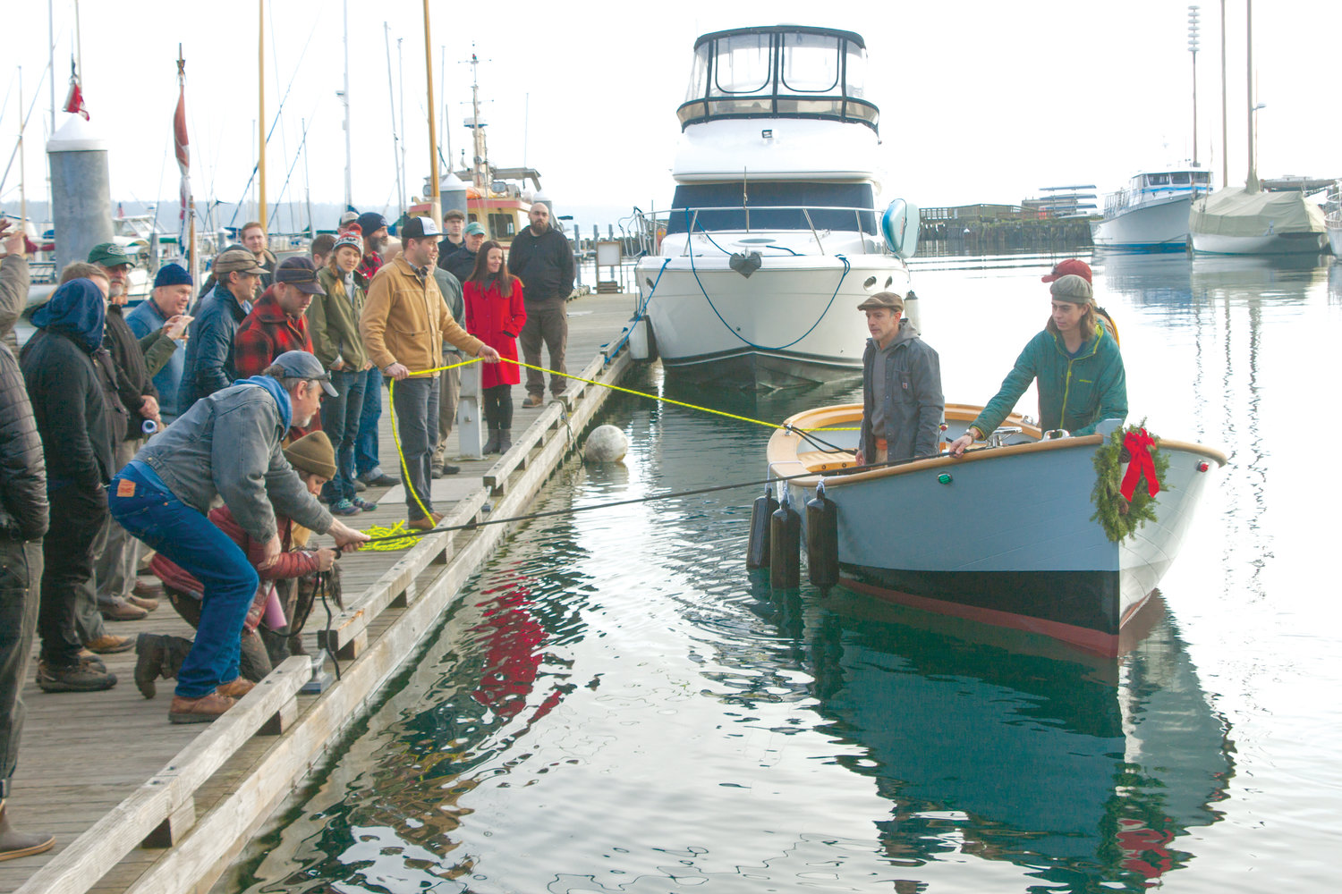 "The Paul Gartside-designed workboat ""Orca"" was the first vessel built by students of the Northwest School of Wooden Boat Building to launch from Point Hudson on the afternoon of Dec. 9, and support crews can be seen here pulling it back to the dock."