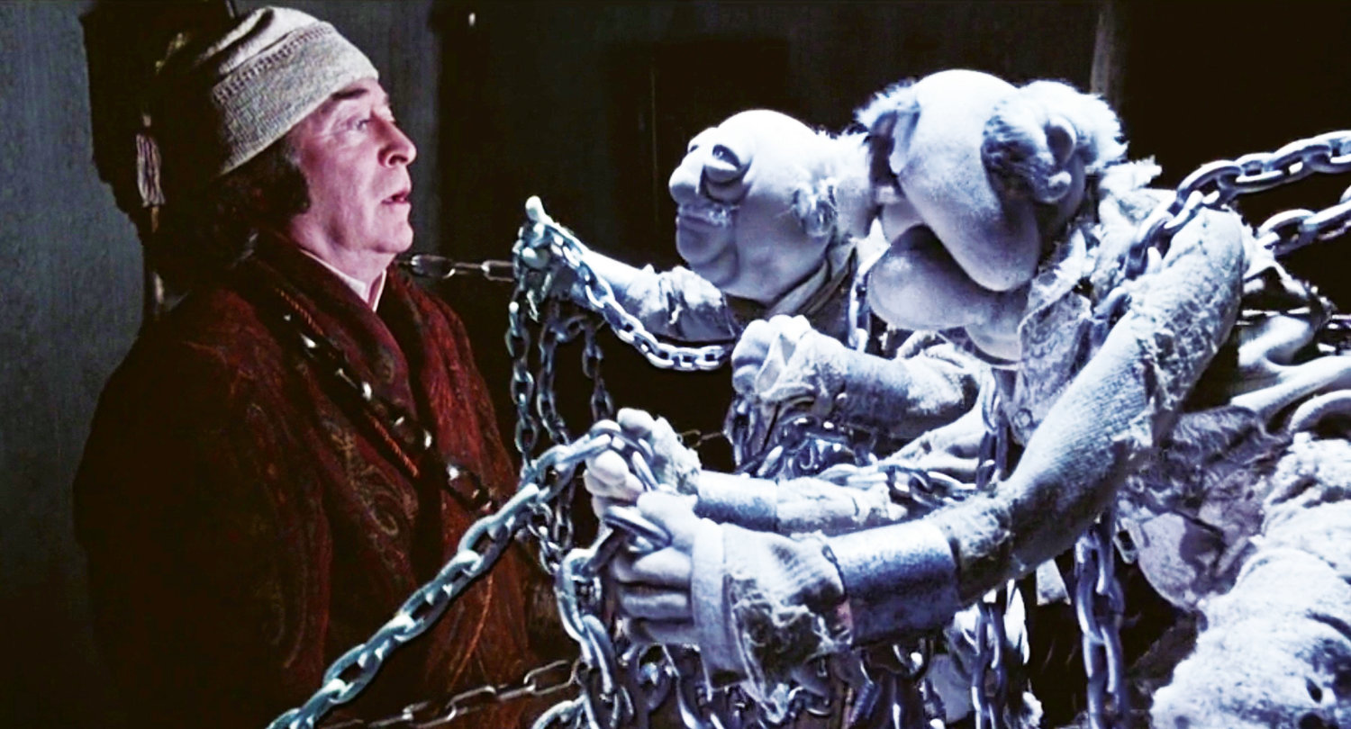 "A different Scrooge (Michael Caine) is haunted by the ghosts of his former business partners, Jacob and Robert Marley (Statler and Waldorf) in 1992's ""The Muppet Christmas Carol."""