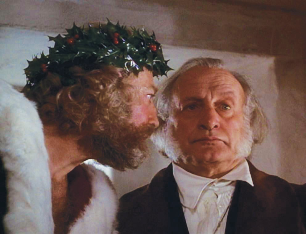 "The Ghost of Christmas Present (Edward Woodward) stares down Ebenezer Scrooge (George C. Scott) in 1984's ""A Christmas Carol."""