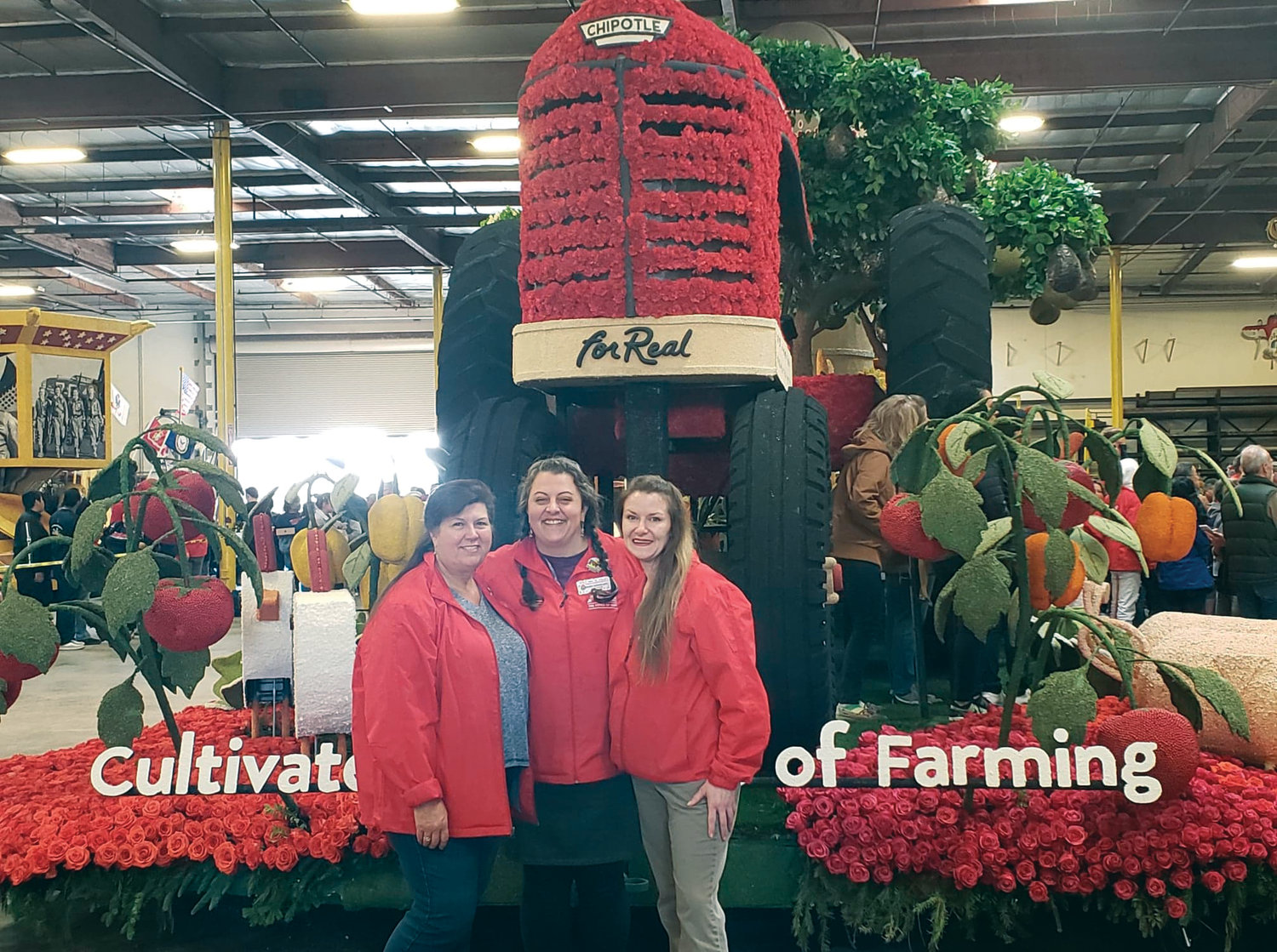 "Sharrai Morgan, owner of Holly's Fine Flowers in Port Townsend, is flanked by members of her ""flower family"" in front of their completed float for the 2010 Rose Parade."