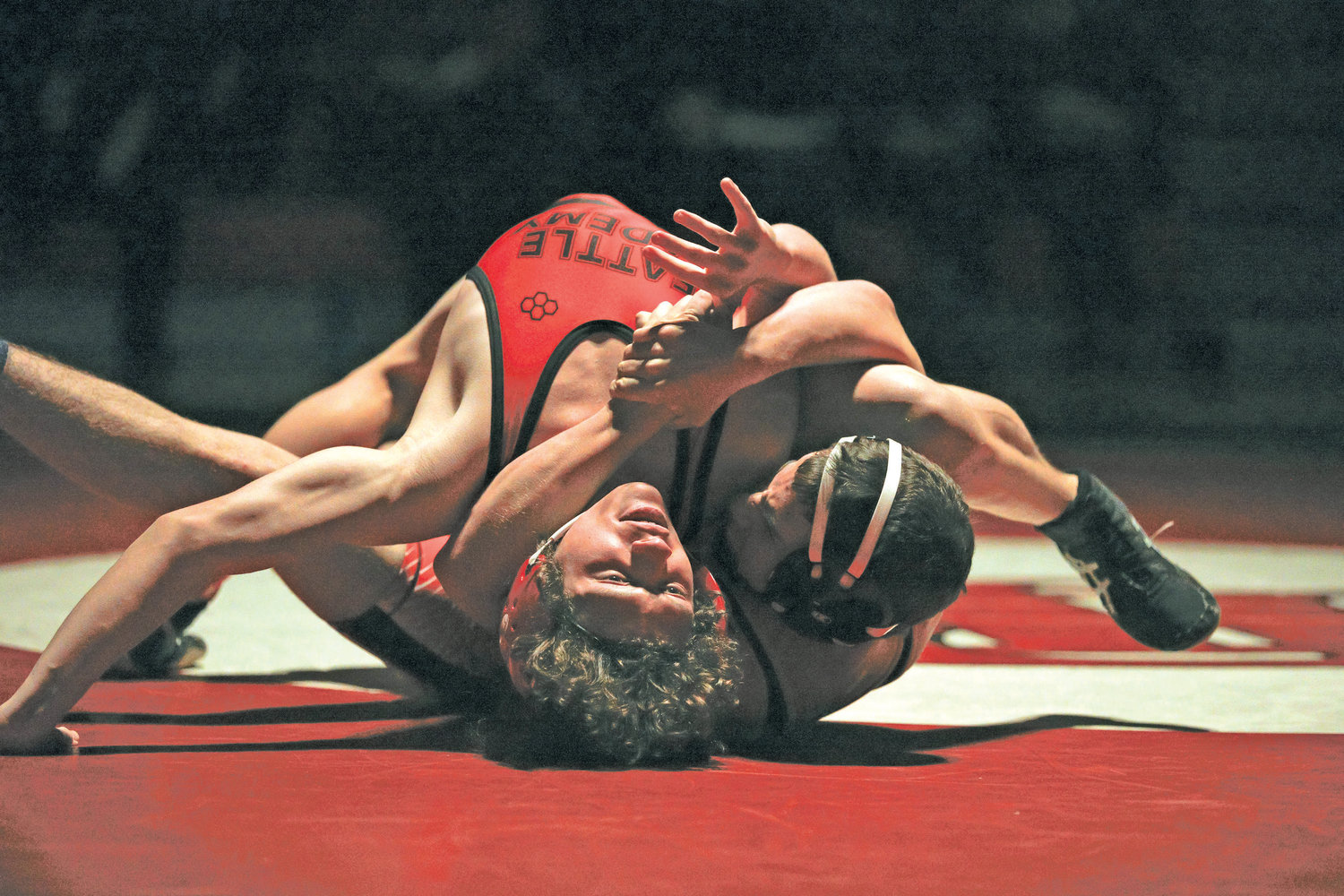 Redhawks wrestler, Ike Banks (bottom), locks his opponent's head and knee together and spreads him open while rolling back to pick up the fall-points.