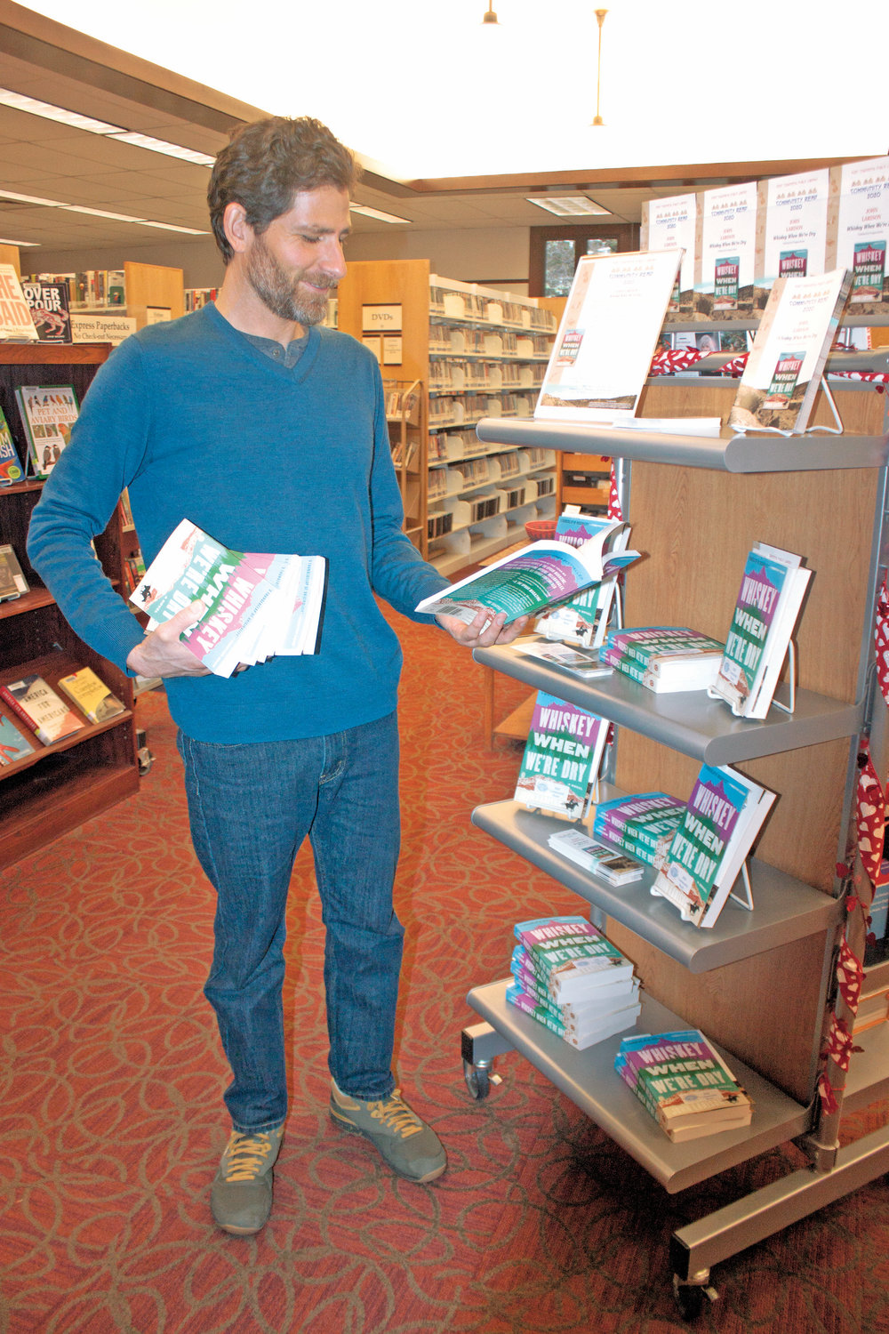 "Keith Darrock, Port Townsend Public Library manager in charge of public and technical services, stocks copies of John Larison's Western novel, ""Whiskey When We're Dry,"" in preparation for the 15th annual Community Read this March."