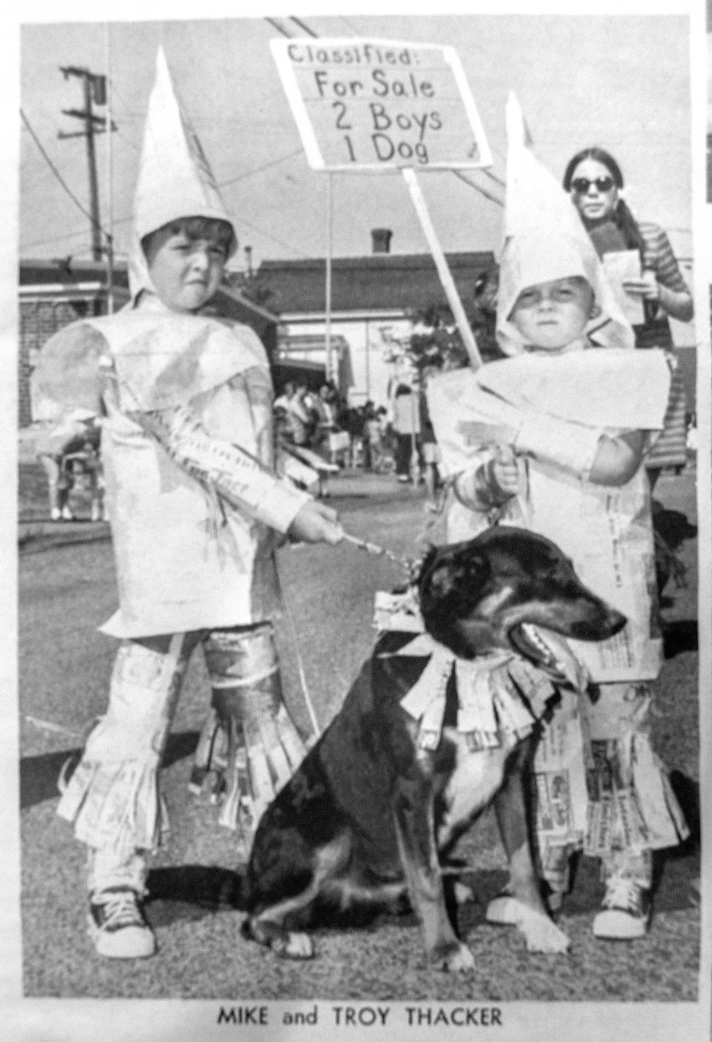 Mike and Troy Thacker dressed up for the 1969 Pet Parade covered in newspaper. Sign reads: For sale 2 boys 1 dog.
