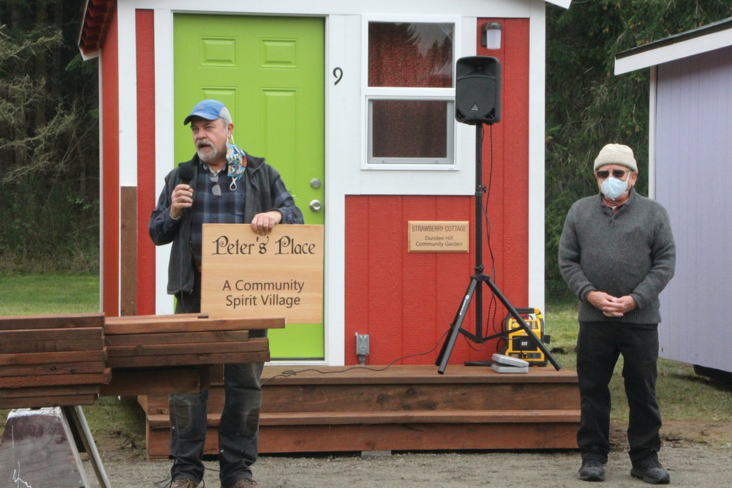 Randy Welle presents Peter Bonyun with a placard honoring his work to construct the 'Peter's Place' tiny home village in Port Hadlock.