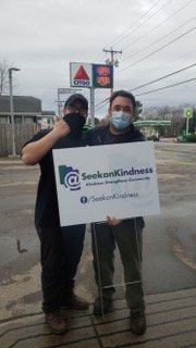 Benjamin Benson and Mike DiPietro prepare to post the SeekonKindness yard sign