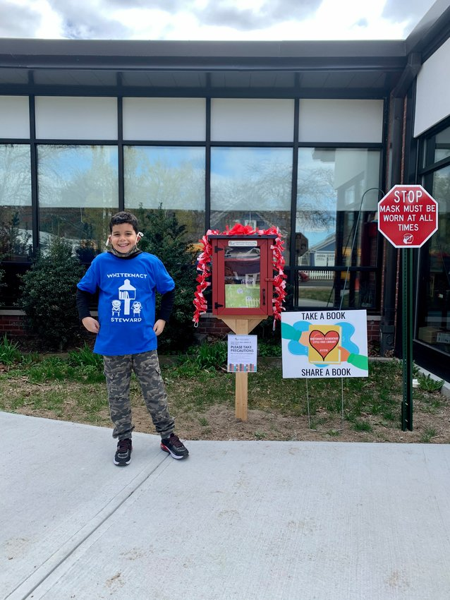 Fifth grade student, Ethan Ibanez poses with the newly installed Little Free Library at Whiteknact Elementary School.