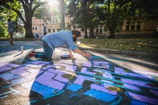 Andrew Oesch paints a mural during the 2020 Rain Harvest Art Festival.