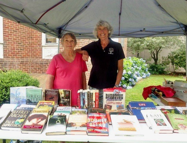 East Prov. Library Friends Rosemarie Sirenski and Lu Rodrigues welcome book lovers to the Weaver Library Farmers Market book sale this summer.