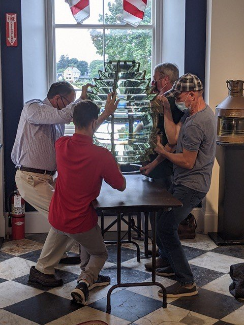 Holding the 225-pound antique glass lens by its brass frame, the moving team lifts it off a high platform onto a table in the first step of the move in Newburyport.