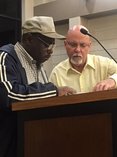 Sealy Public Works Director Mark Pulos, right, reviews documents with resident Lenel Brandiberg, who went before the city council Dec. 12 with concerns about drainage on Live Oak Street.