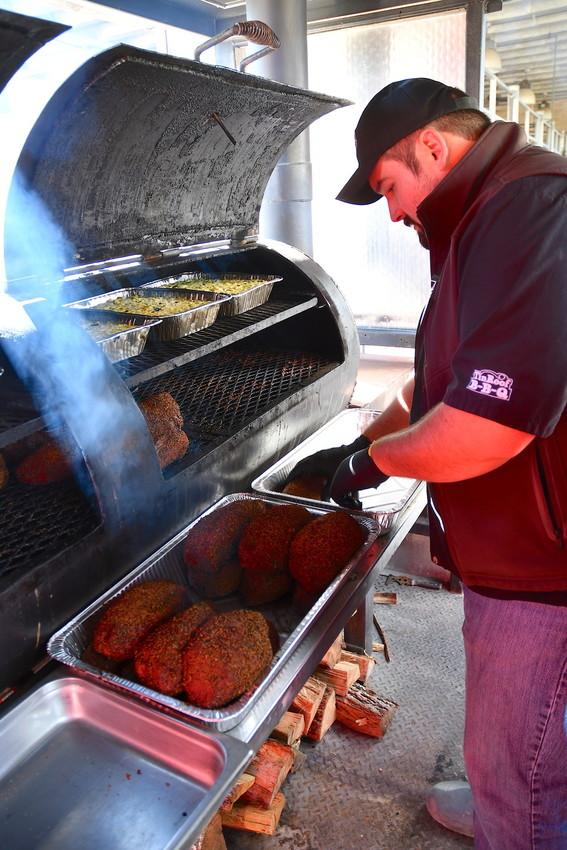 Brek Webber from Tin Roof BBQ in Atascocita pulls smoked sirloing from the pit at the recent barbecue town hall meeting at Texas A&M University in College Station.
