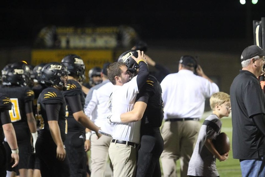 Assistant coach Kamm Coker embraces a player following the Tigers' win over West Columbia in their final regular season to put them in the playoffs. It was the Tigers first time seeing the postseason since 2015.