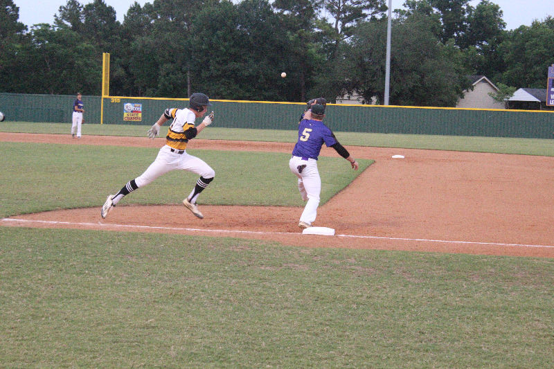 Sealy's Justin Eckhardt races to beat a Navarro throw to first base during the Tiger's loss in the second game of the three-game series in La Grange.