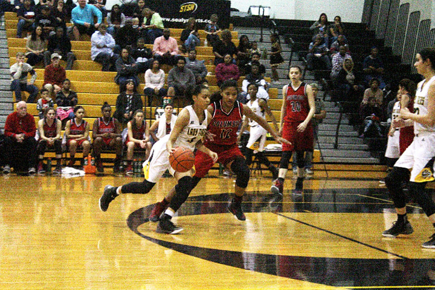 Sealy's Kayla Green drives around a Columbus defender during the Lady Tigers loss on Friday at home.