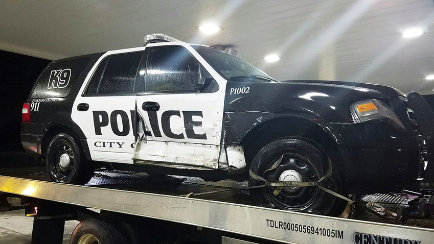 Sealy Police Officer Eric Gum's patrol vehicle rests on the bed of a tow truck early Monday morning after it was struck on Interstate 10.