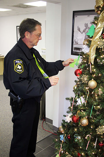 The Angel Tree is up once again at The Sealy News to celebrate the Christmas season and the gift of giving. Ornaments adorn the tree featuring names of local Sealy residents from its two senior living facilities, Silver Lake and The Oaks. Pictured is Sealy Police Chief Chris Noble picking an ornament off last year's Angel Tree.