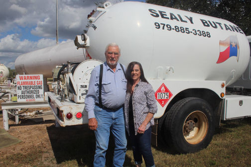 Leon and Linda Kollatschny, owners of Sealy Appliance & Butane Co., stand ready in front of a butane tanker awaiting their next customer.