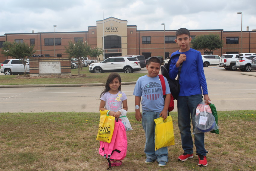 From left to right, Jatziry and Edgar Vargas and Leo Acosta show off their new supplies they'll get to use when they return to school Aug. 27