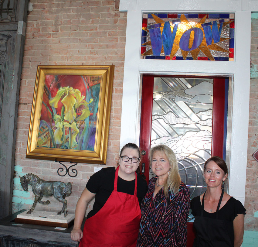 From left, Bailey Briggs, Annette Hadjdik Smith and Shannon Boulet pose in front of the 'Wow window' at the Studio Blend Gallery & Coffee Shop in downtown Sealy.