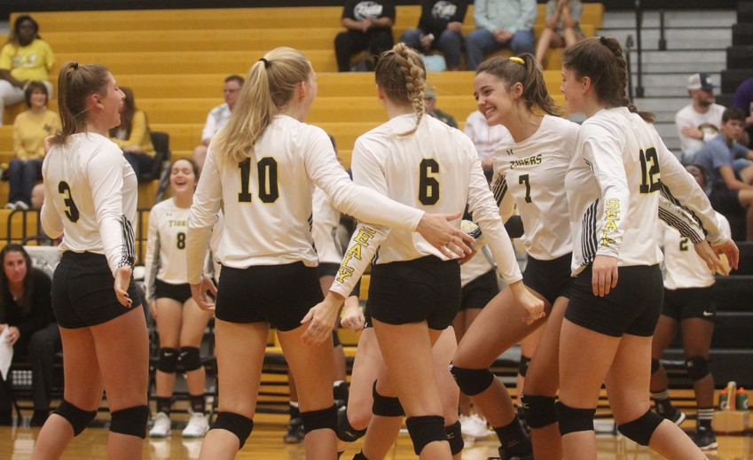 Sophomore Ally Dickens (7) celebrates one of her three kills against Fulshear with her teammates.