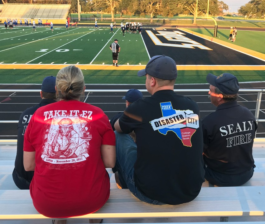 Kelly Zapalac and Sealy Firefighters watch along as the Sealy Tigers take care of the Bay City Blackcats.