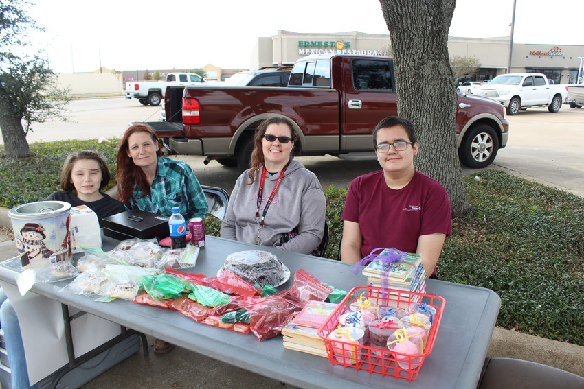 Dylan Bunn, Cortni Breman, Kim Avilez and Robert Avilez sat in the Tractor Supply parking lot Sunday raising funds for the Interact Club and accepting new and used books for Books for the World.