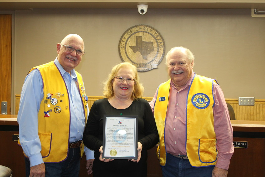Robert Fait and Bill Blume of the Sealy Lions Club accept a proclamation from Mayor Pro Tem Sandra Vrablec honoring the club's 50th anniversary.