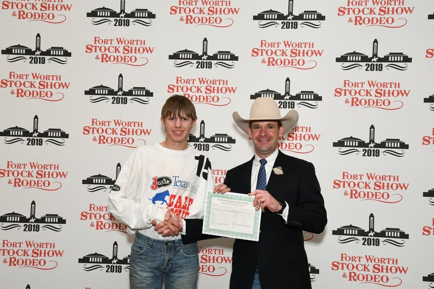 Cameron Hein, a member of Sealy FFA, caught a calf during Fort Worth Stock Show & Rodeo's Calf Scramble, earning a $500 purchase certificate presented by Paxton Motherall, a Calf Scramble committee member.