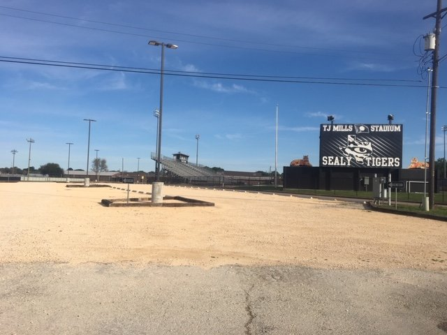 Sealy ISD officials were granted a variance allowing them until January to install asphalt replacing a gravel parking lot near Tiger Stadium.