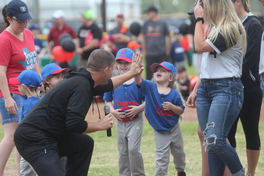 Sealy High School Athletic Director Shane Mobley shares a high-five with a young athlete.