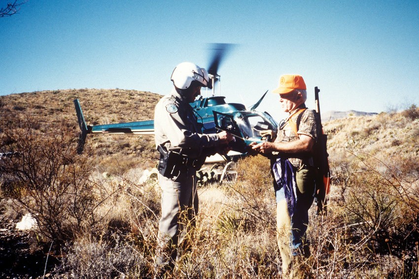 In a remote part of the Big Bend, a warden checks the licenses of two hunters after arriving by helicopter. The warden and helicopter pilot were the only other people the hunters saw during their hunt.