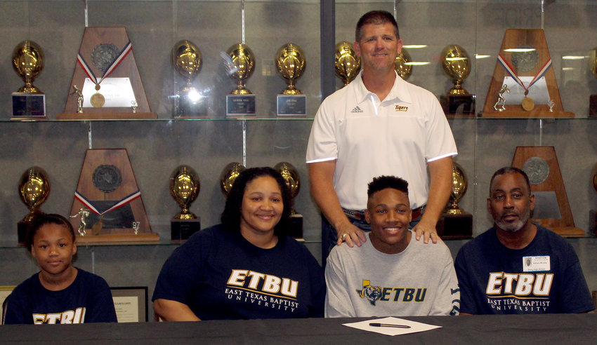 Remaining a Tiger; A.J. McGee noted it was a simple decision to sign on with a team that shared a mascot and celebrated his commitment to East Texas Baptist University Friday afternoon in the Sealy High School gym lobby. Joining him, from left, are sister Z'Ryiah, mother Chrissy, head coach Shane Mobley (standing) and father Adrian.
