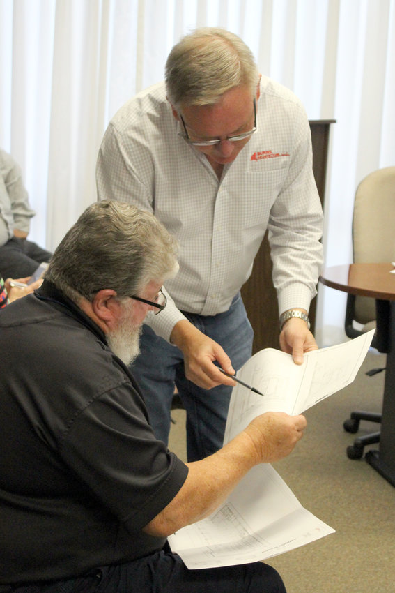 Architect Kenny Burns (standing) shows diagrams for the new EMS station in Sealy to EMS Director Ron Dille during the Austin County Commissioners Court meeting Monday morning.