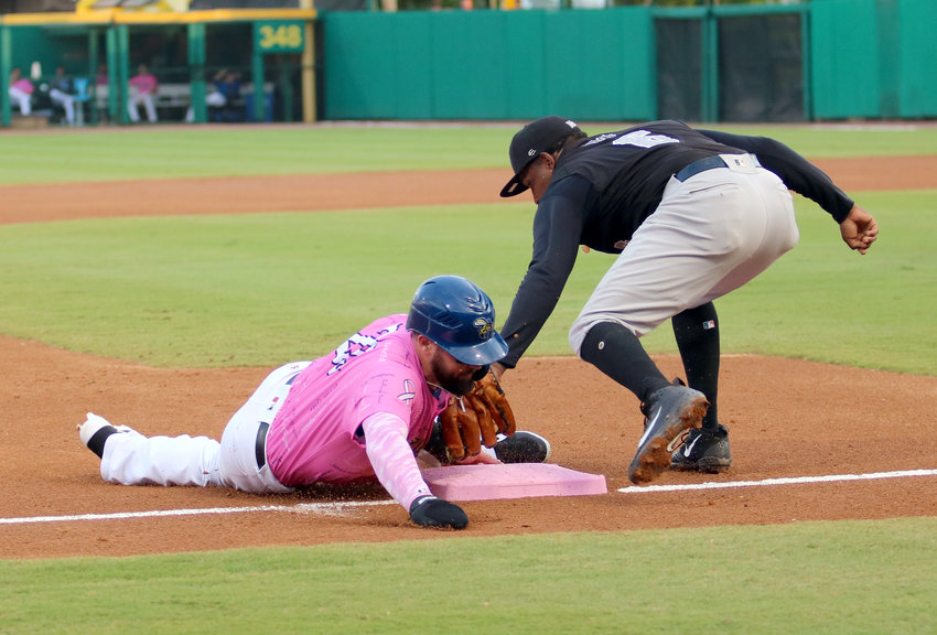 Jason Martinson slides safe into third during Friday's game against the York Revolution. The Skeeters lost 9-6 but took five of seven games last week from the York. Friday's game was the annual Pink in the Park game for breast cancer awareness.